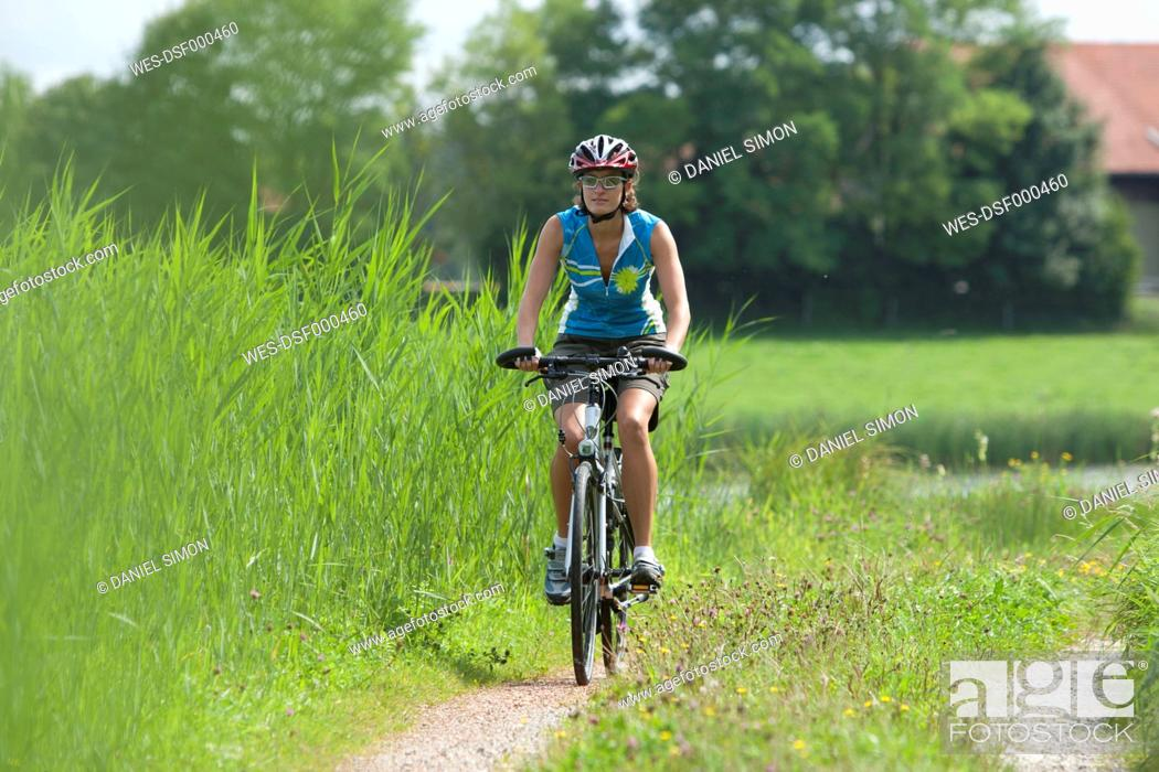 Stock Photo: Germany, Bavaria, Mid adult woman riding bicycle.