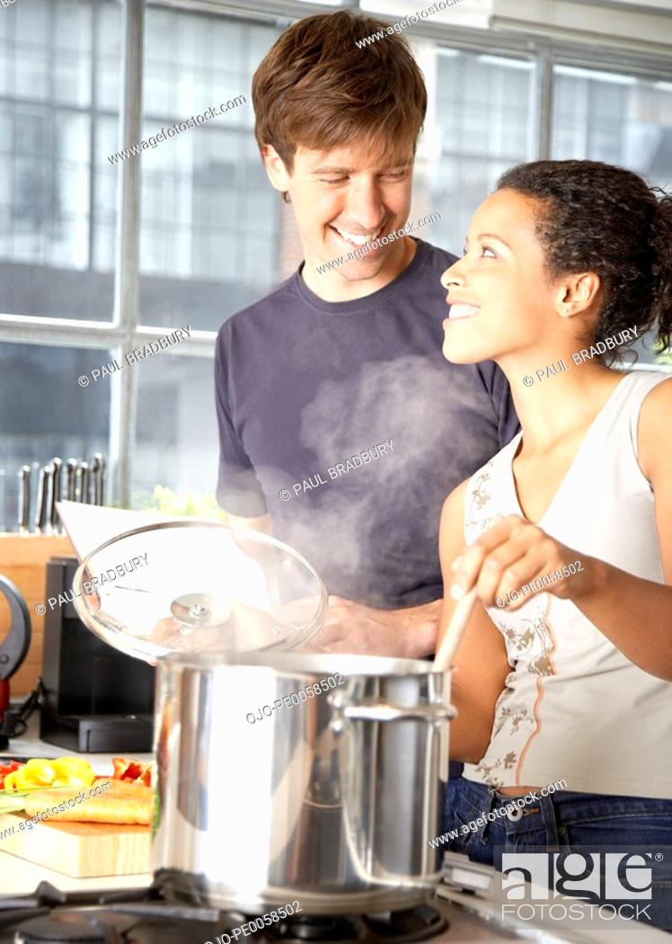 Stock Photo: Couple making meal in kitchen.