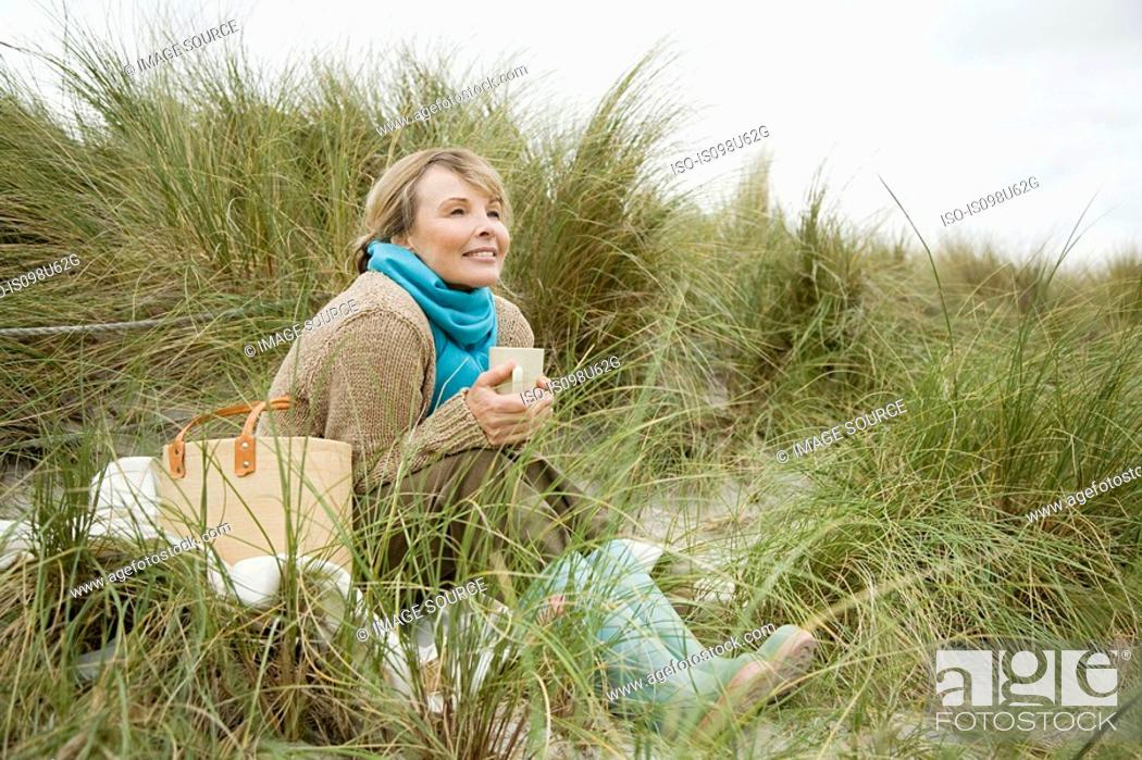 Stock Photo: Woman on dune with hot drink.