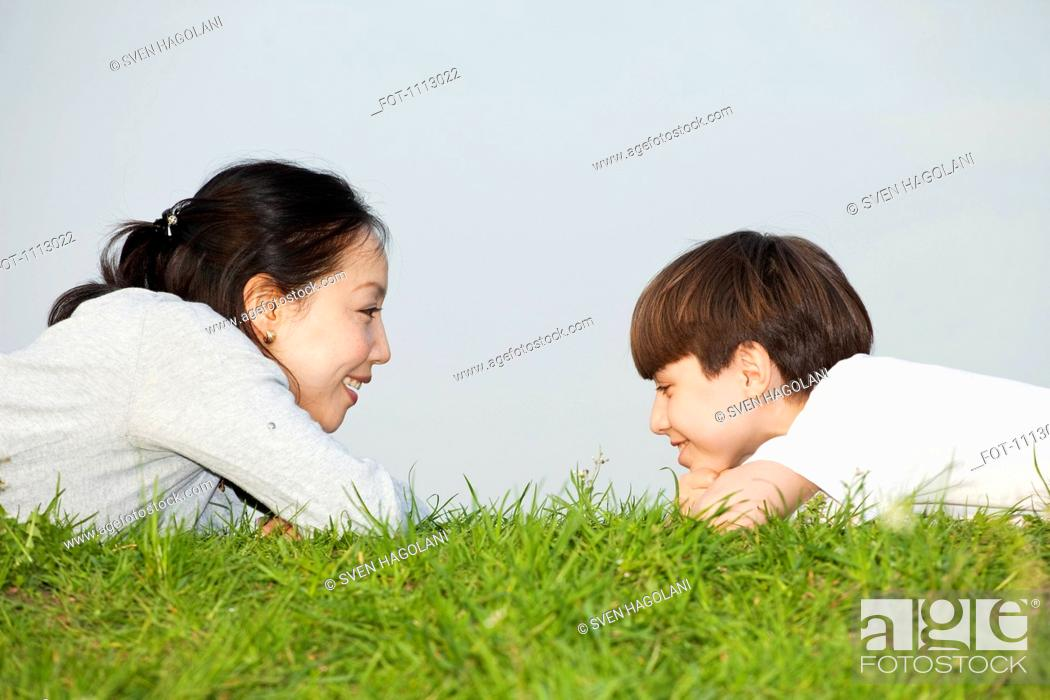 Stock Photo: A mother and son lying on their stomachs face to face.