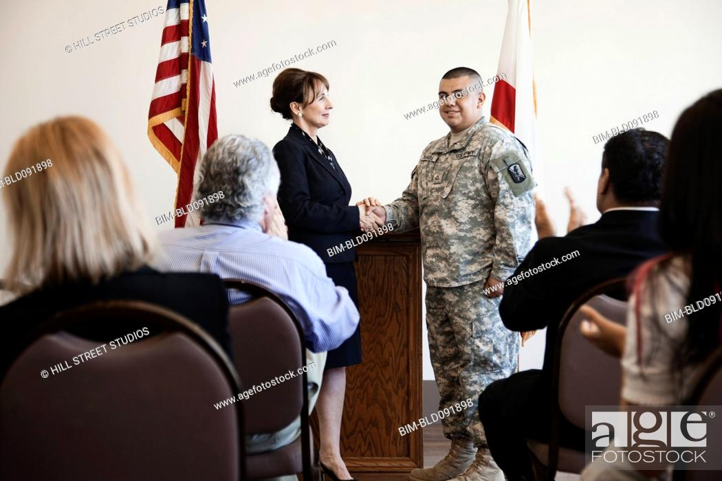 Stock Photo: Politician greeting soldier at political gathering.