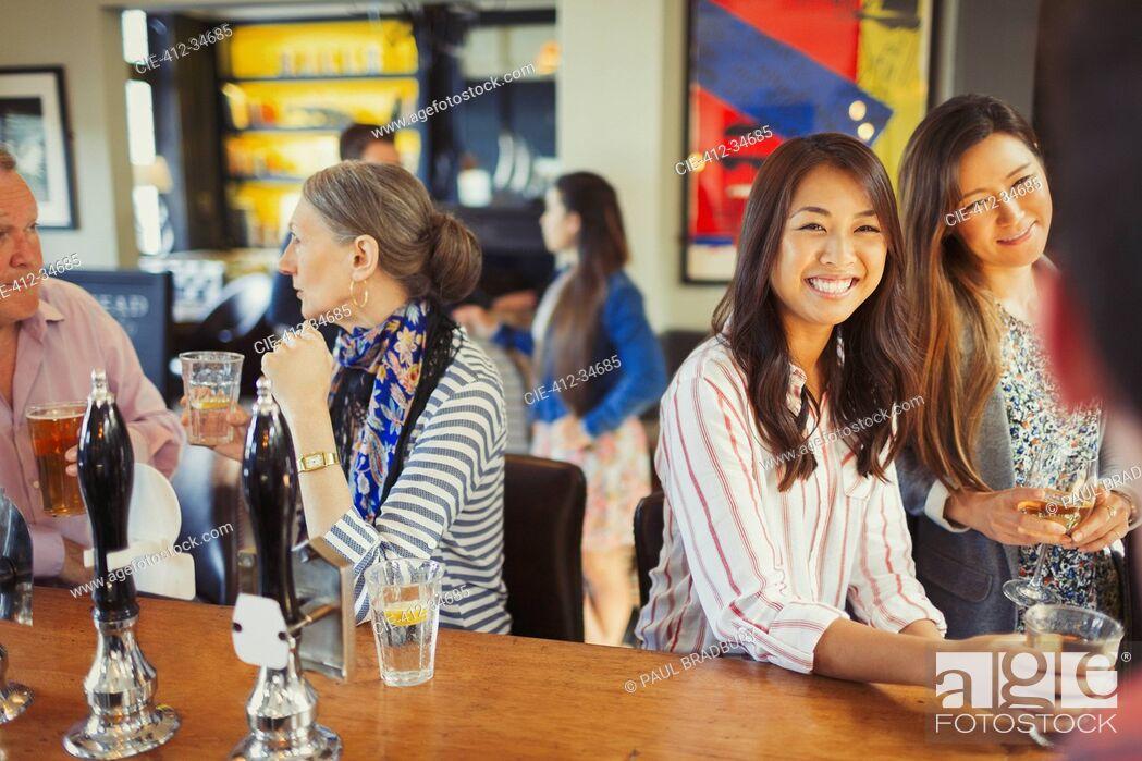 Stock Photo: Women smiling at bartender and drinking at bar.