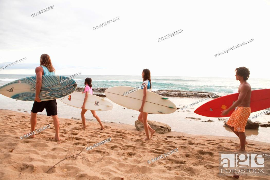 Stock Photo: Four young friends carrying surfboards on beach.