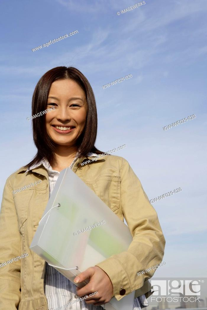 Stock Photo: Portrait of a young woman with a folder in her hand.