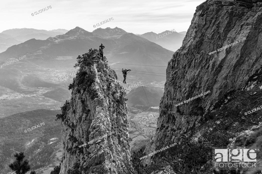 Stock Photo: An hiker over a tibetan bridge at via ferrata delle Aquile. Paganella, Trento, Trentino, Italy.