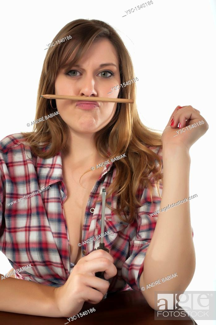 Stock Photo: Bored handywoman playing with pencil and screwdriver.