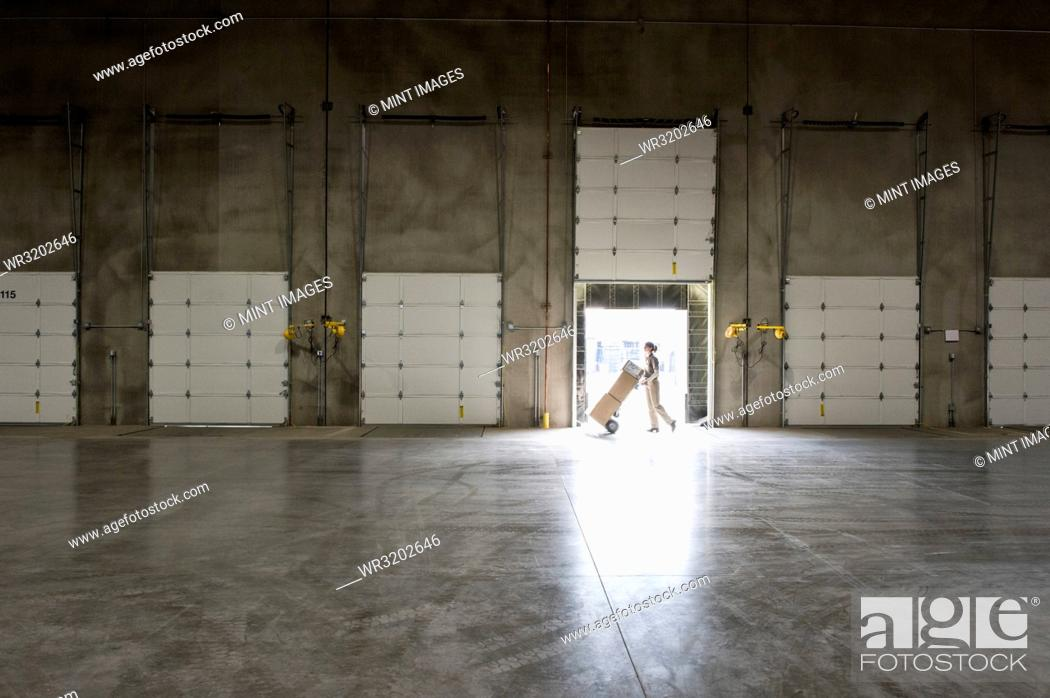Imagen: A warehouse worker with a hand truck walking past an open loading dock door in a large distribution warehouse.