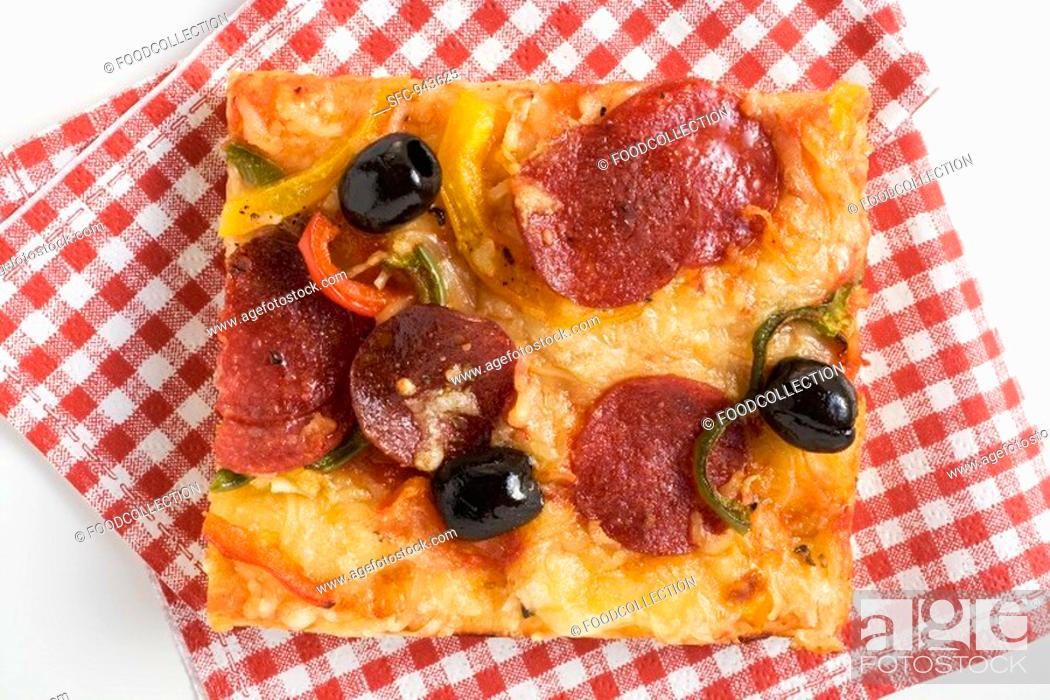 Stock Photo: A slice of salami pizza with peppers and olives.