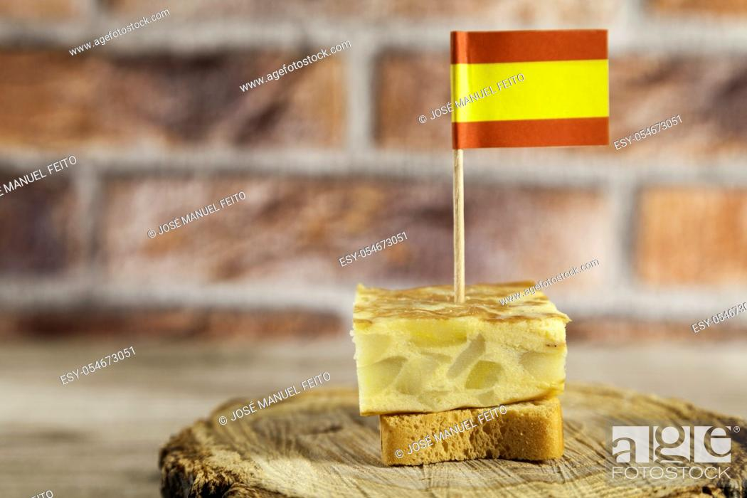 Stock Photo: Spanish omelette brochette with spanish flag on a wood slice on wooden table and red brick background.