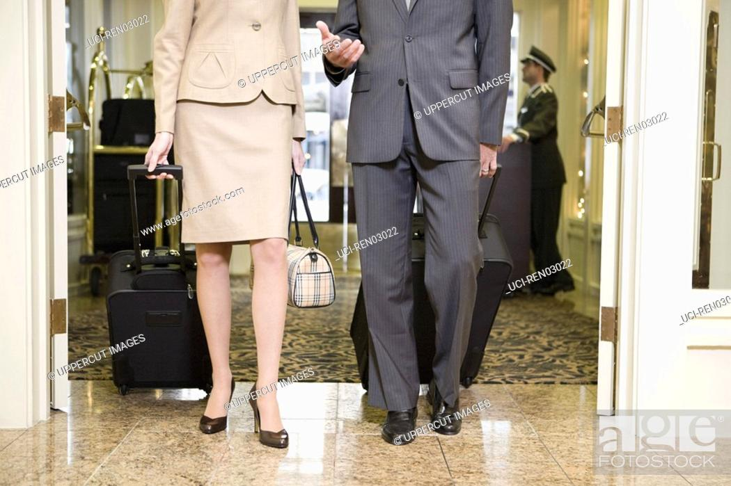 Stock Photo: Couple pulling suitcases in lobby.