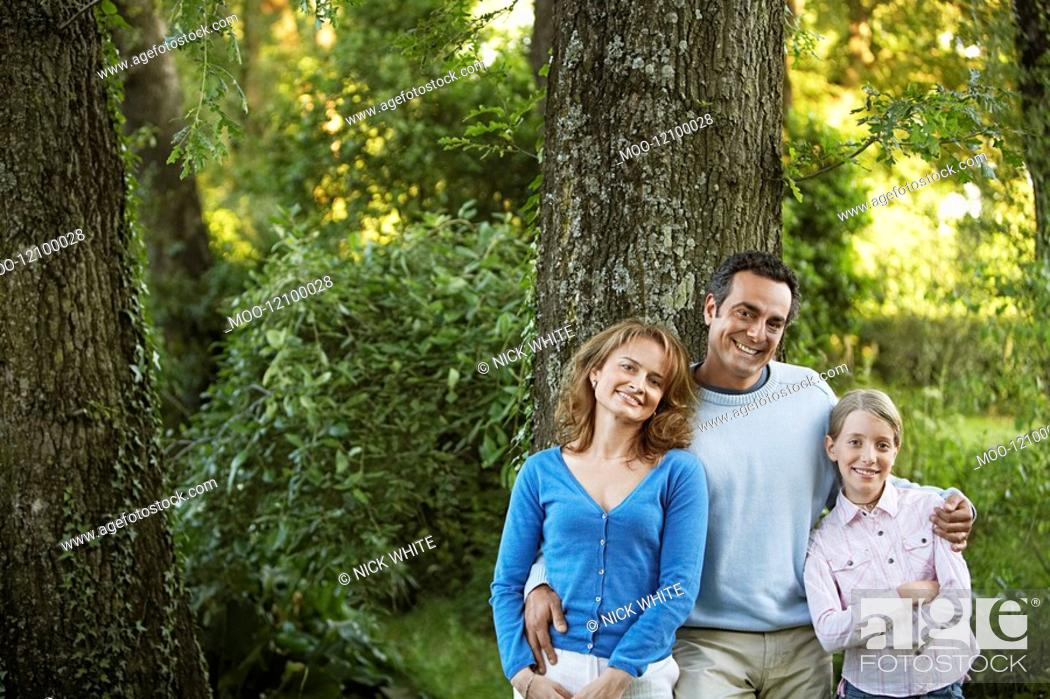 Stock Photo: Young girl with parents leaning on tree in park portrait.