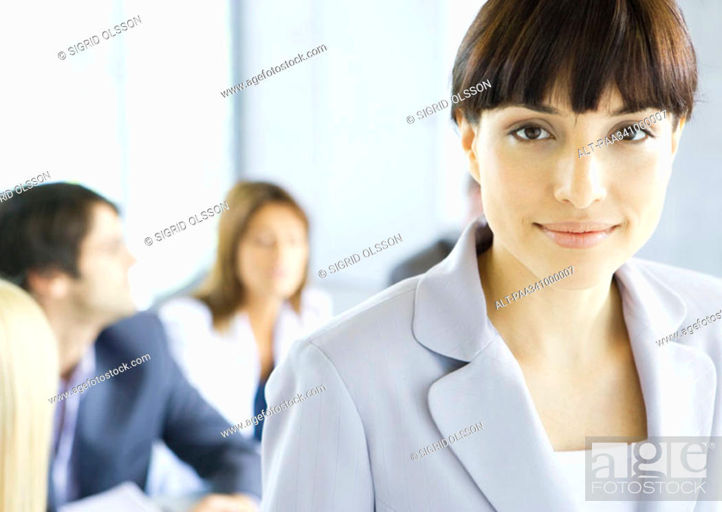 Stock Photo: Businesswoman smiling at camera, meeting in background, portrait.