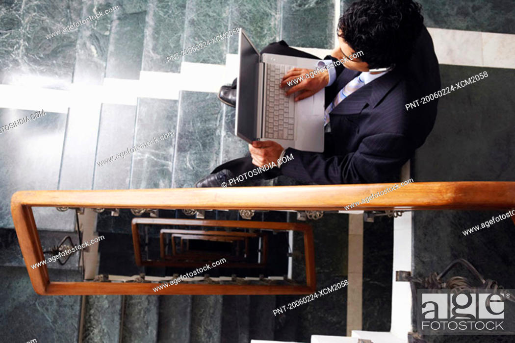 Stock Photo: High angle view of a businessman sitting on the staircase and using a laptop.