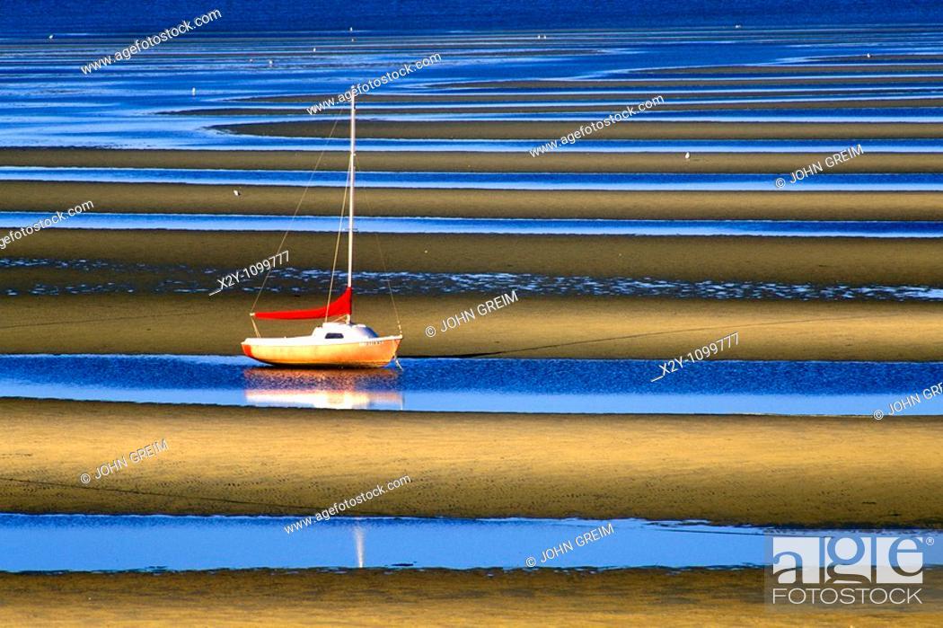 Stock Photo: Sailboat anchored in tidal flats, Cape Cod Bay.