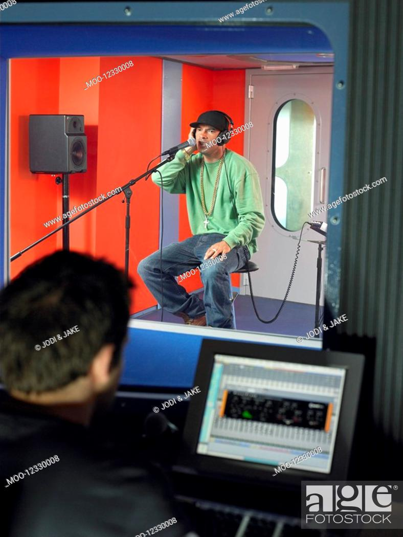 Stock Photo: Young man singing in studio technician in foreground.