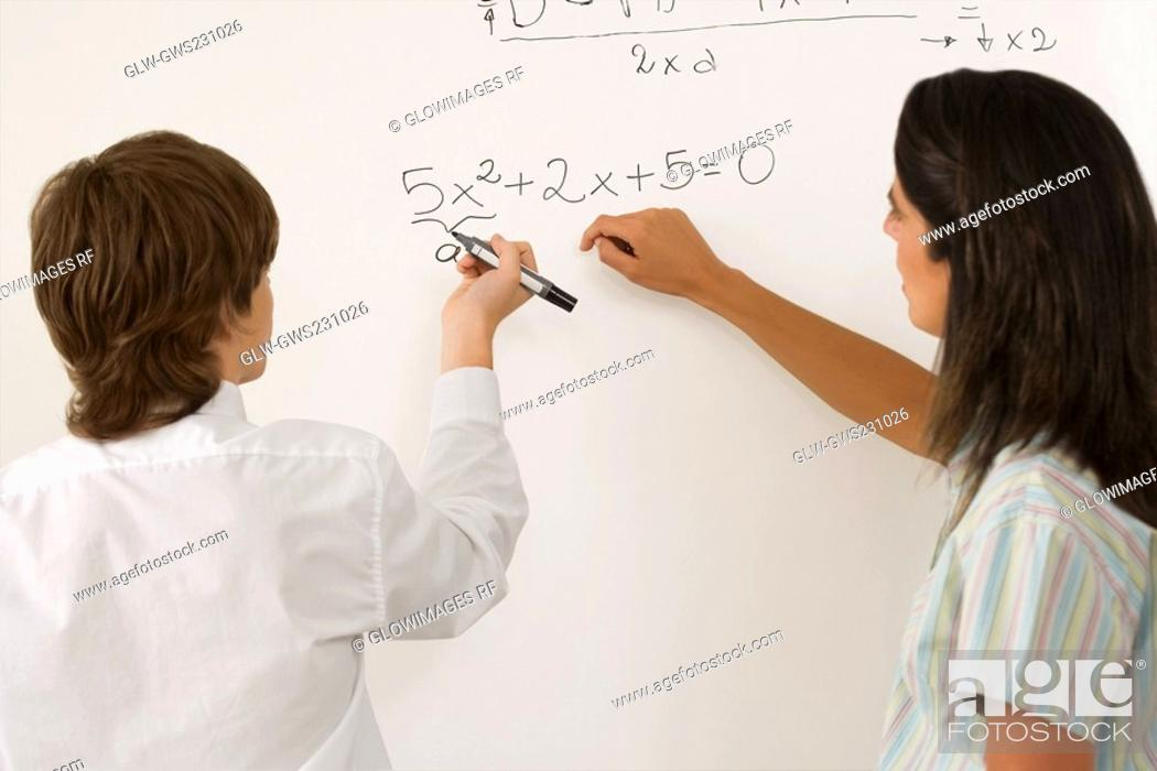Stock Photo: Rear view of a teenage boy solving algebra on whiteboard and a female teacher standing beside him.