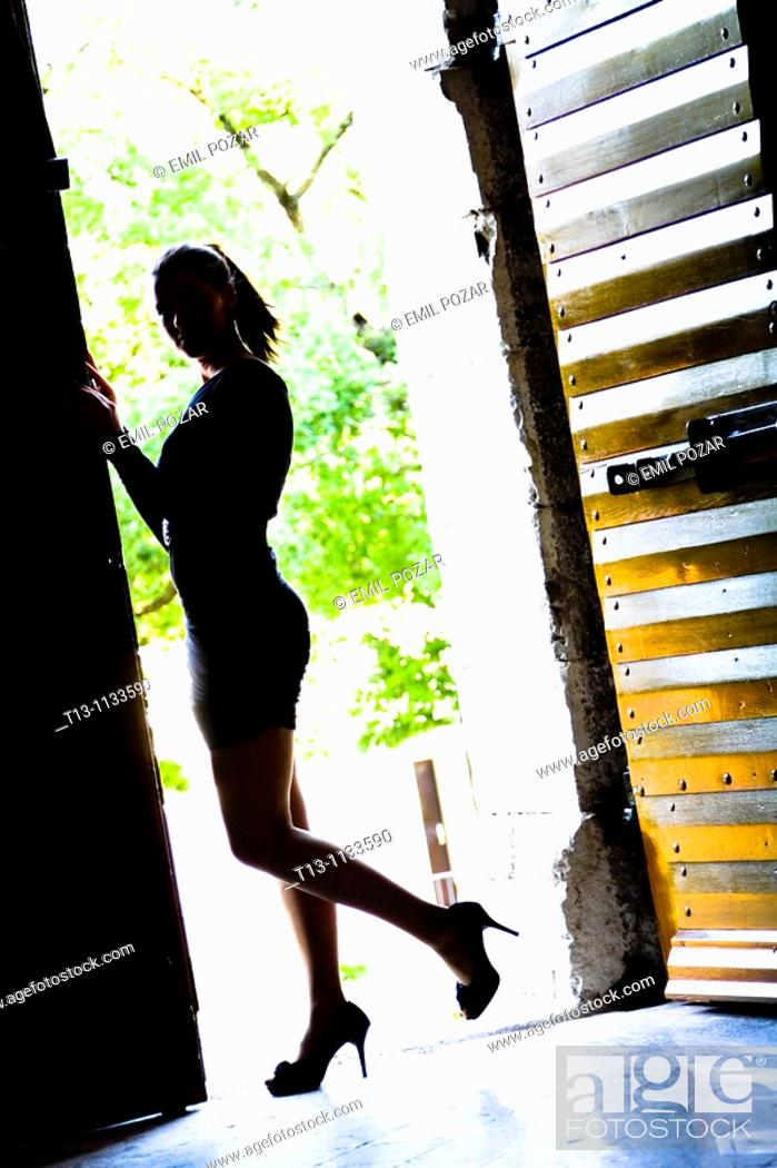 Stock Photo: Silhouette of young woman on the entrance.
