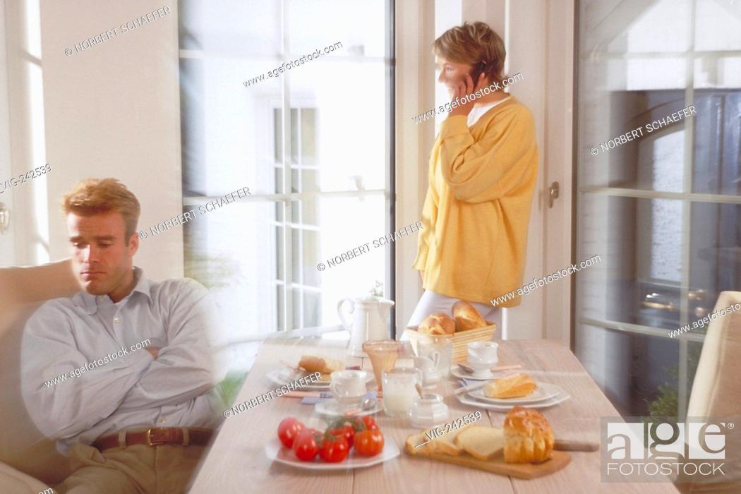 Stock Photo: indoor, half-figure, couple mid of 30, man sits angry at breakfast whiles she is standing at the window making a phone call  - GERMANY, 02/03/2005.