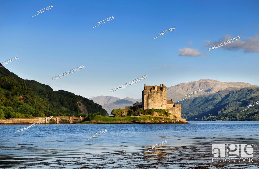 Stock Photo: Restored Eilean Donan Castle on Eilean Donan Island with stone arch footbridge at sundown with Glenelg mountains Scottish Highlands Scotland.