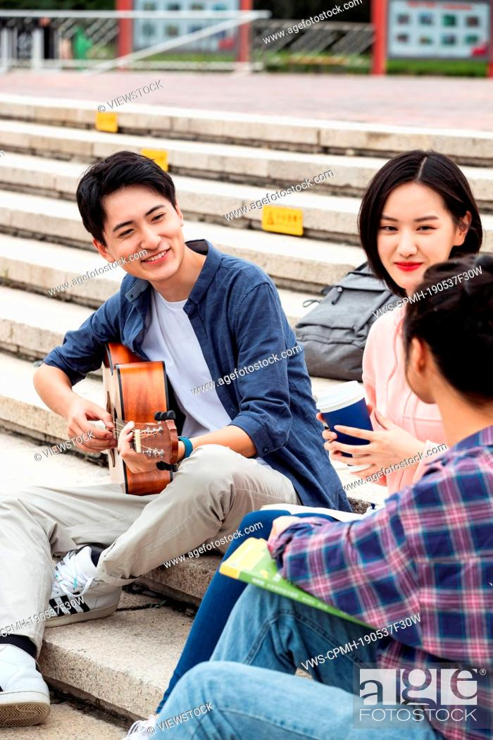 Imagen: The young college students sat on the steps to play guitar to sing.