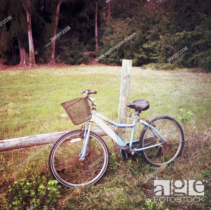 Stock Photo: A bicycle sitting beside a barb wire fence in the countryside.