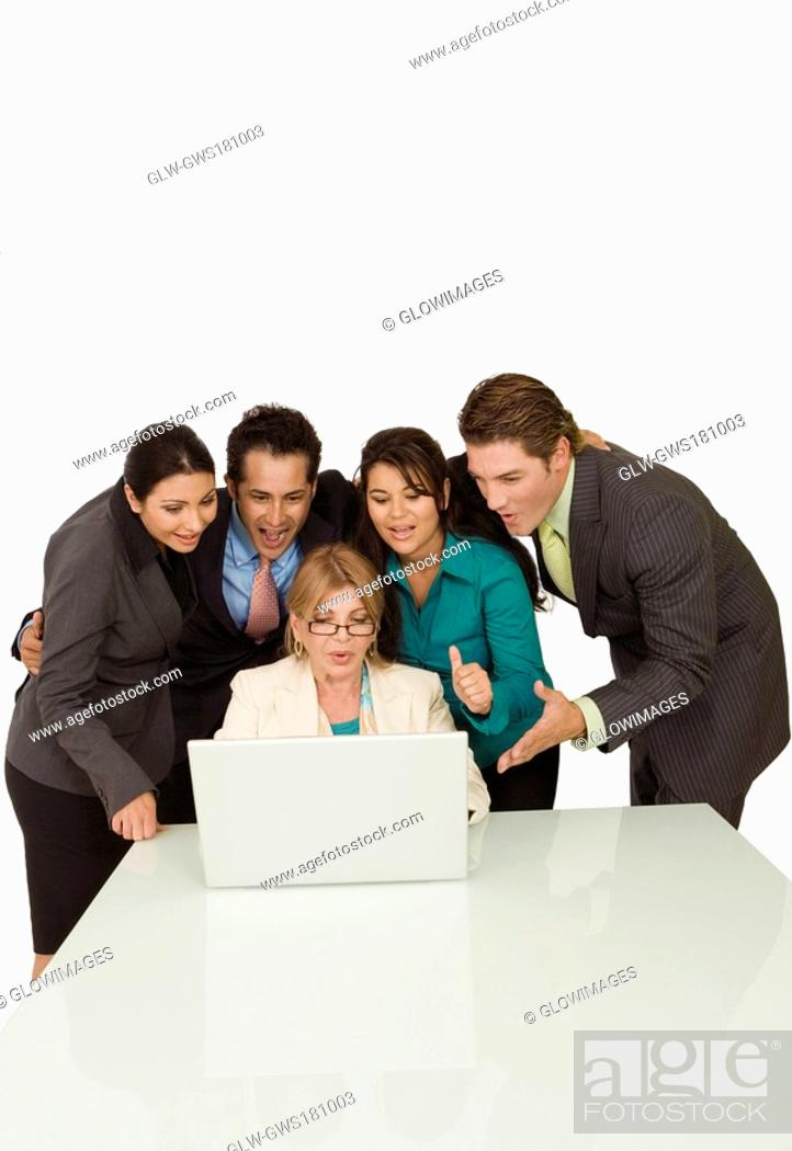 Stock Photo: Businesswoman working on a laptop with four business executives standing beside her.