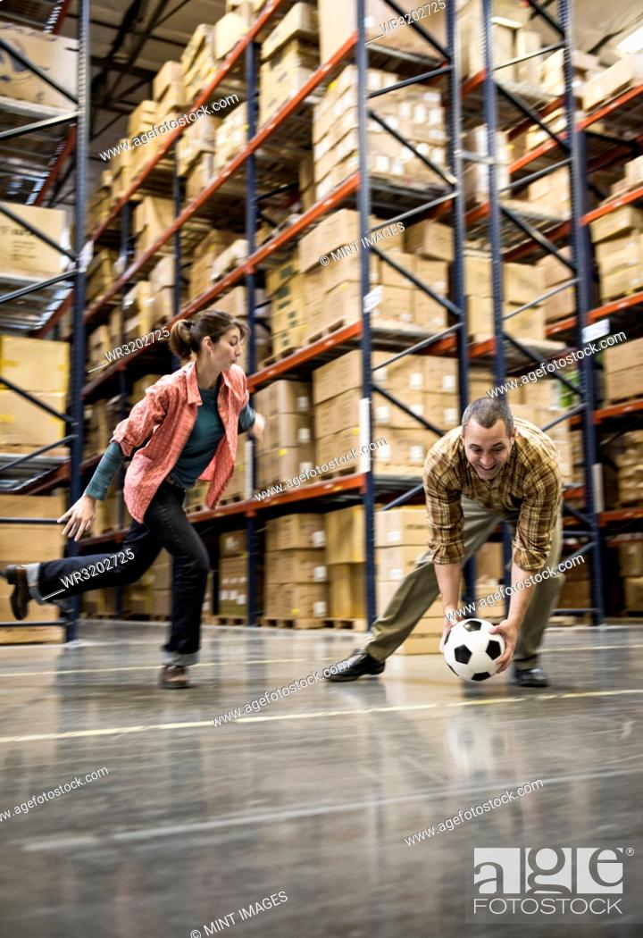 Stock Photo: Two warehouse workers playing soccer during a work break in a distribution warehouse.