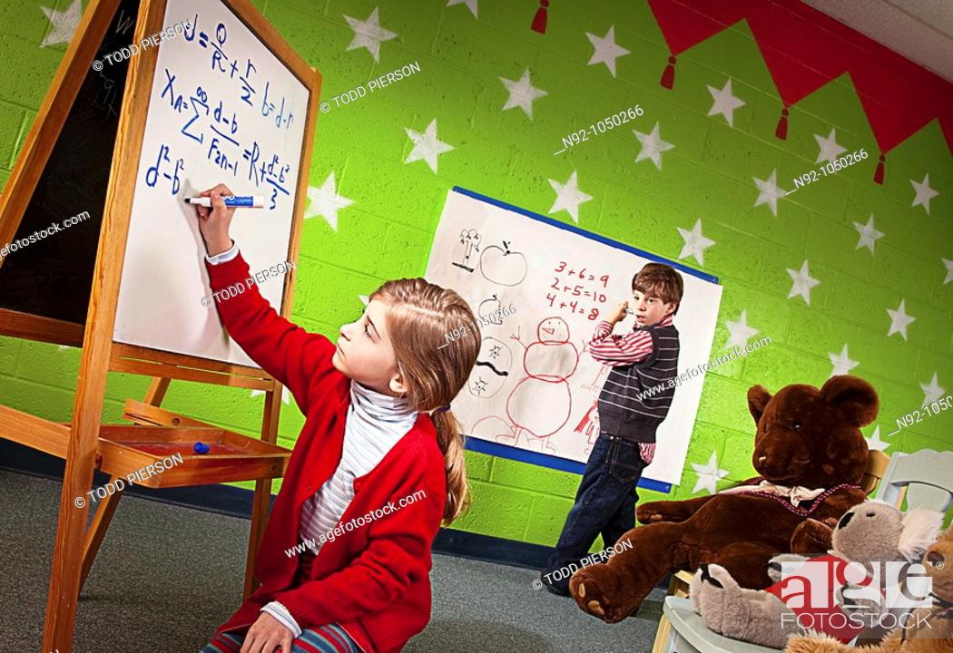 Stock Photo: Little girl writing amazing math problem on board while boy looks on in amazement.