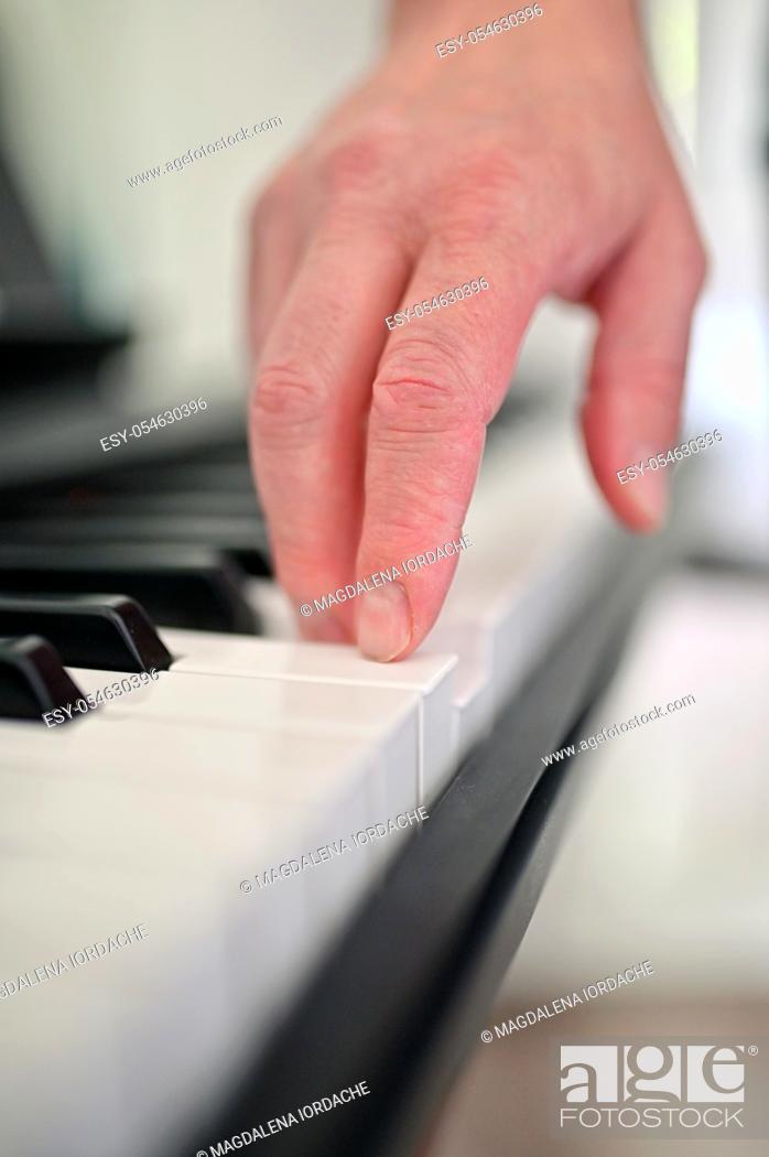 Stock Photo: Closeup Piano Keys And Man Finger.