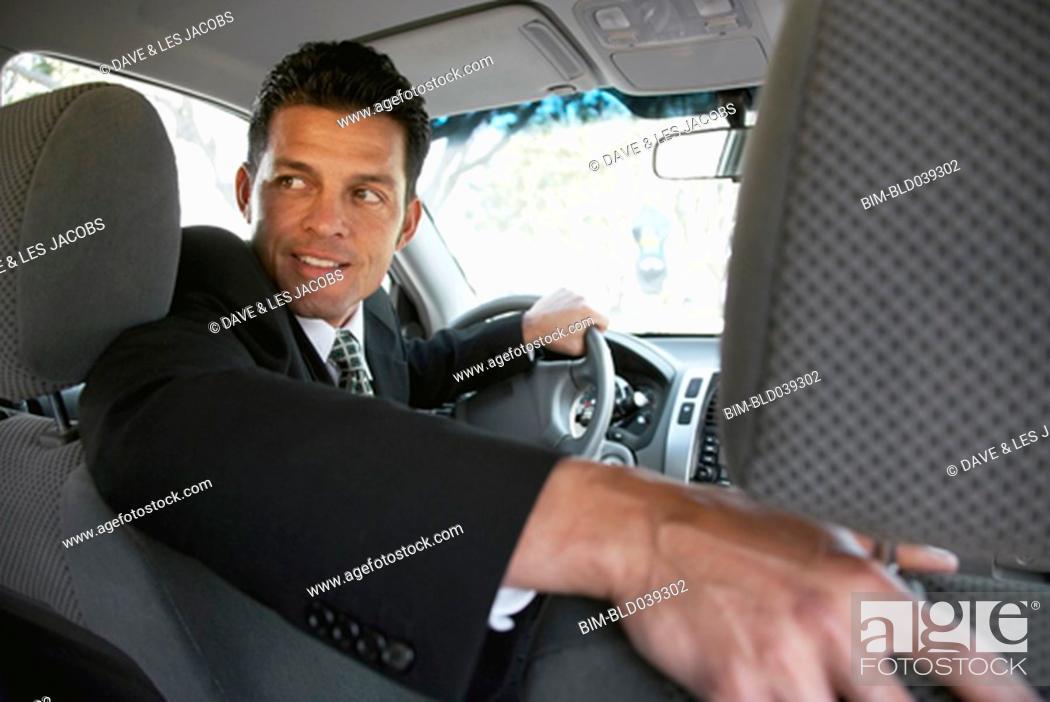 Stock Photo: Hispanic businessman backing up car.