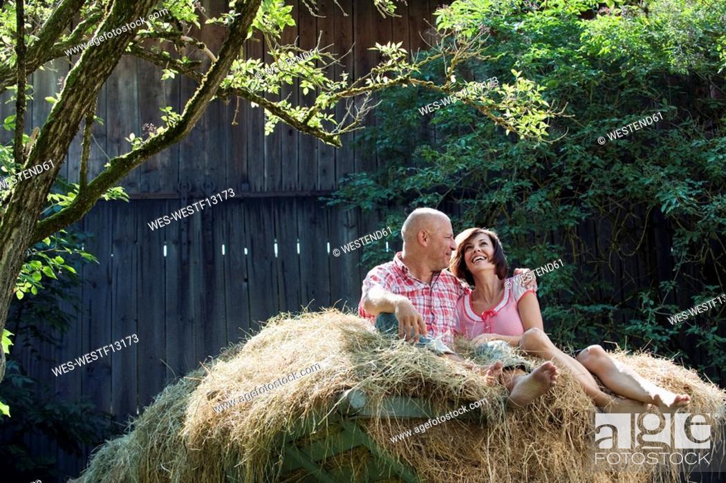 Stock Photo: Germany, Bavaria, Couple sitting on haystack, smiling, portrait.