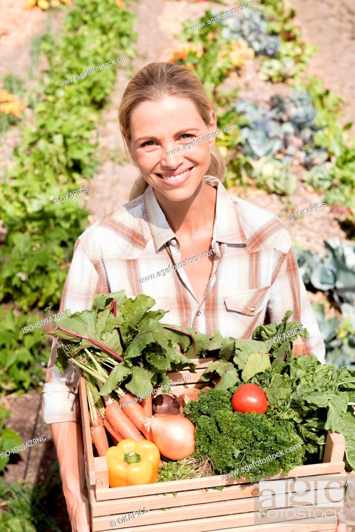 Stock Photo: Portrait of mature woman in garden, holding crate of fresh vegetables.