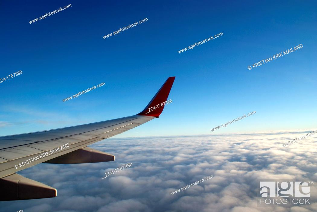 Stock Photo: Looking out on wing af jetplane above the clouds.
