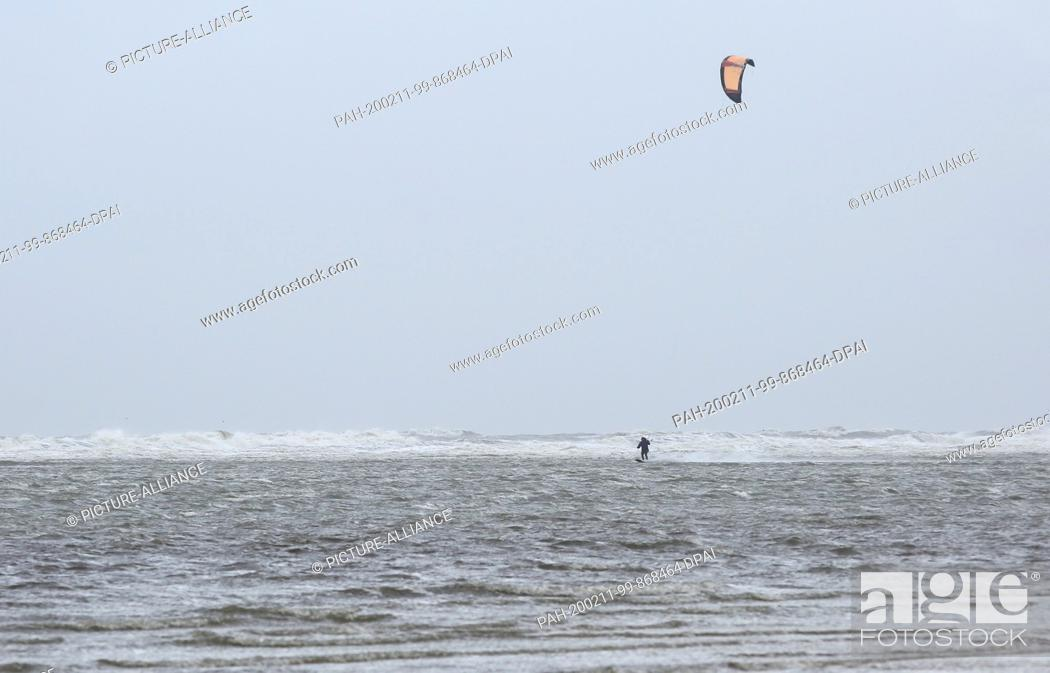 Stock Photo: 11 February 2020, Schleswig-Holstein, St. Peter-Ording: A kitesurfer is on the beach of St. Peter-Ording in rising water.