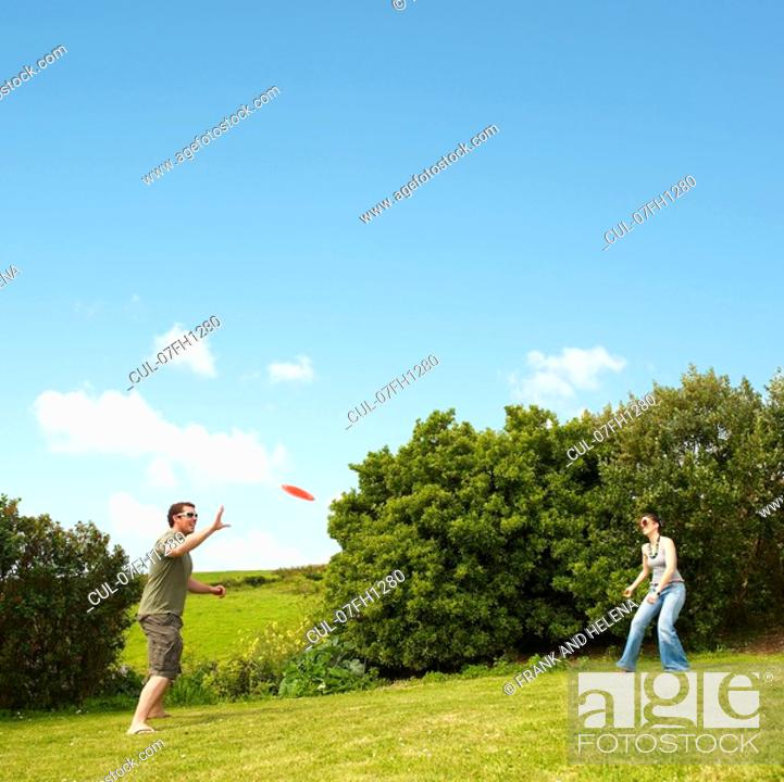 Stock Photo: Couple playing frisbee.