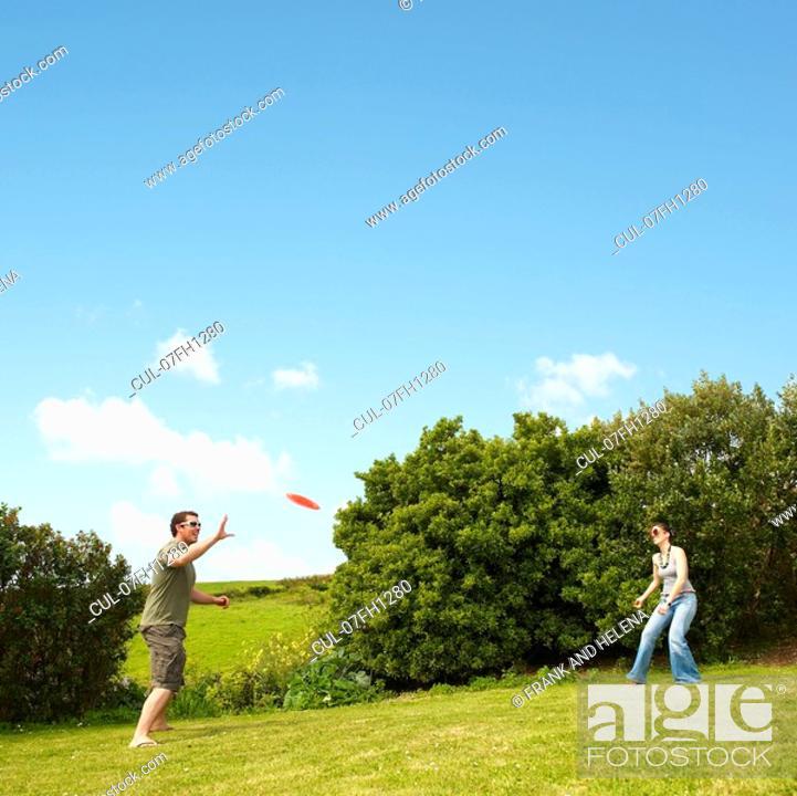 Stock Photo: Couple playing frisbee.