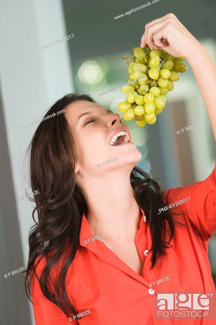 Stock Photo: Woman eating grapes.