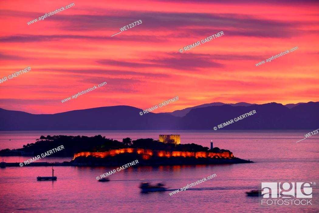 Stock Photo: Red sky sunset at Kusadasi Turkey Harbour with lit Guvercin Adasi Island Genoese castle on the Aegean Sea with mountains of Samos Greece.