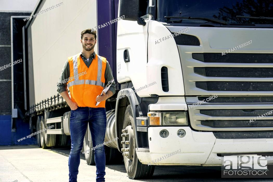 Stock Photo: Worker standing in front of lorry.