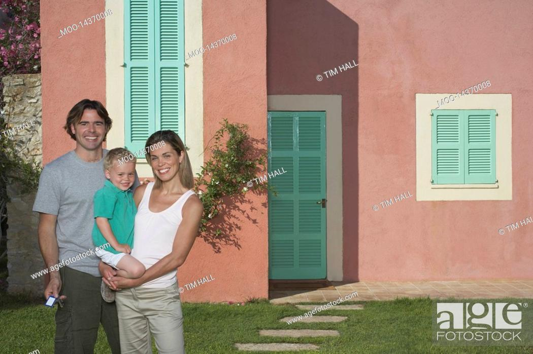 Stock Photo: Portrait of family with boy 2-3 in front of house.