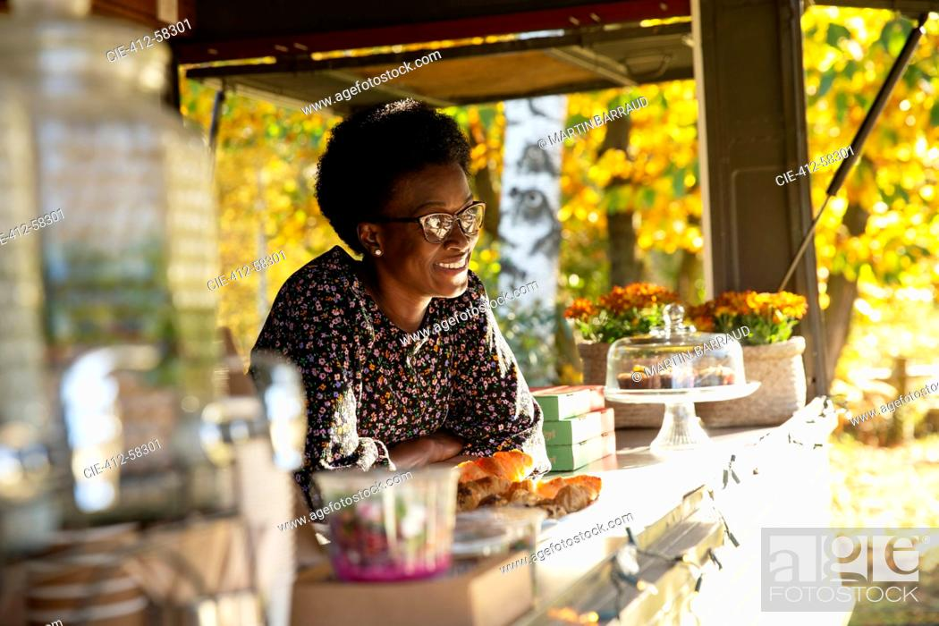 Stock Photo: Happy female food cart owner in sunny park.