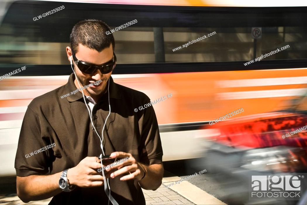 Stock Photo: Young man listening to an MP3 player.