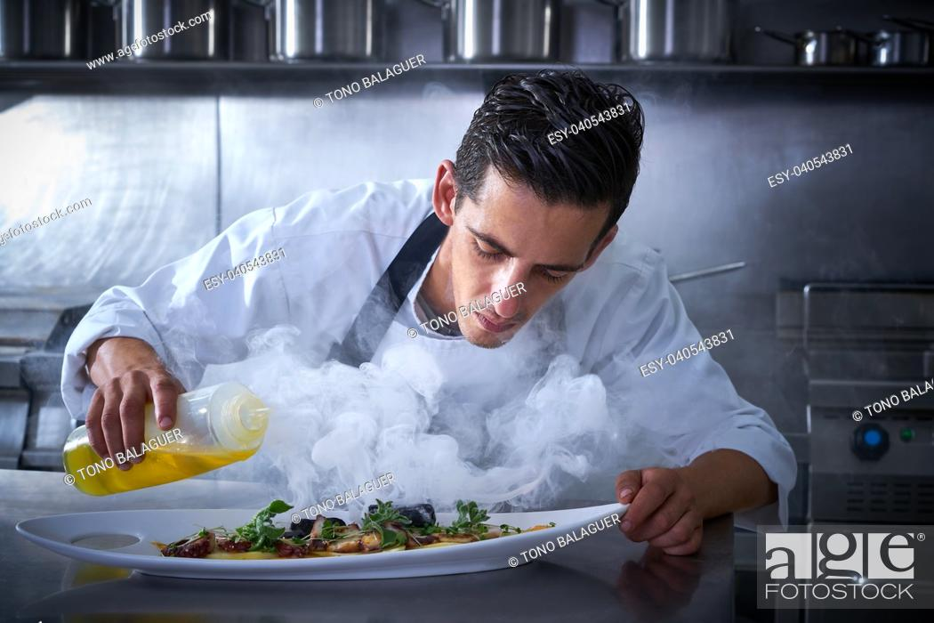 Photo de stock: Chef working in kitchen with smoke and oil at restaurant.