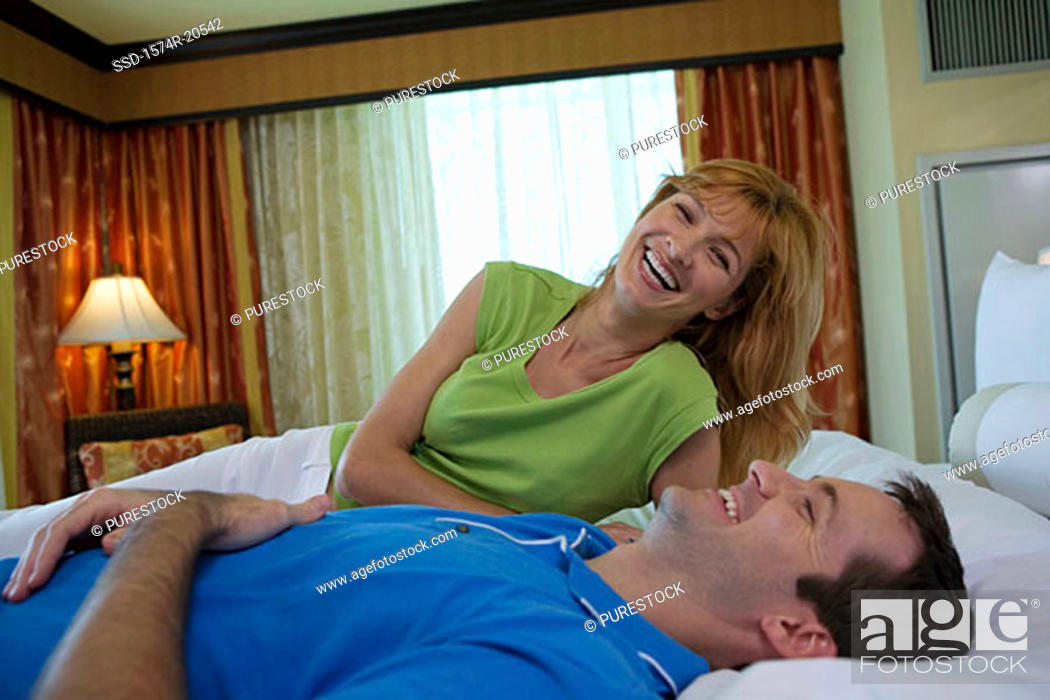 Stock Photo: Young couple lying on the bed and smiling.
