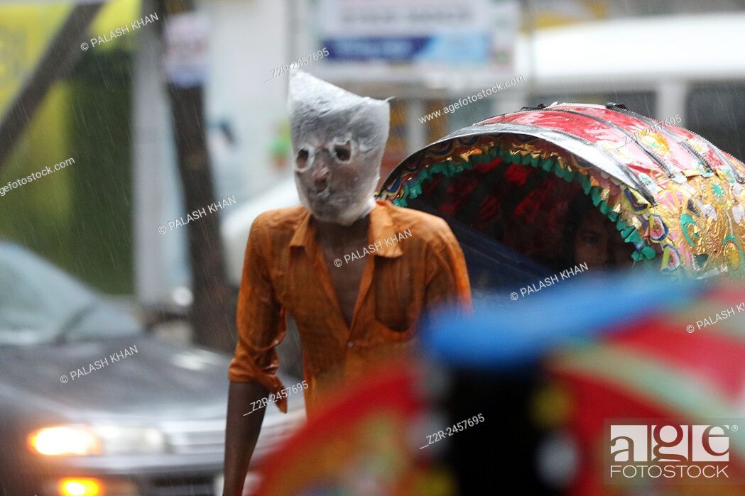 Stock Photo: Rickshaw puller wears a plastic bag on his head and face as he carries passengers in a rain-soaked street of Dhaka, Bangladesh, 13 June 2015.