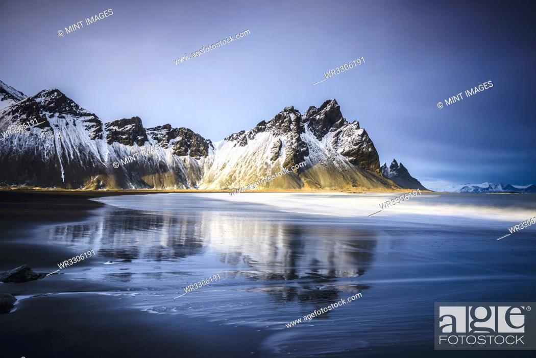 Stock Photo: Ocean waves on beach under snowy mountains.