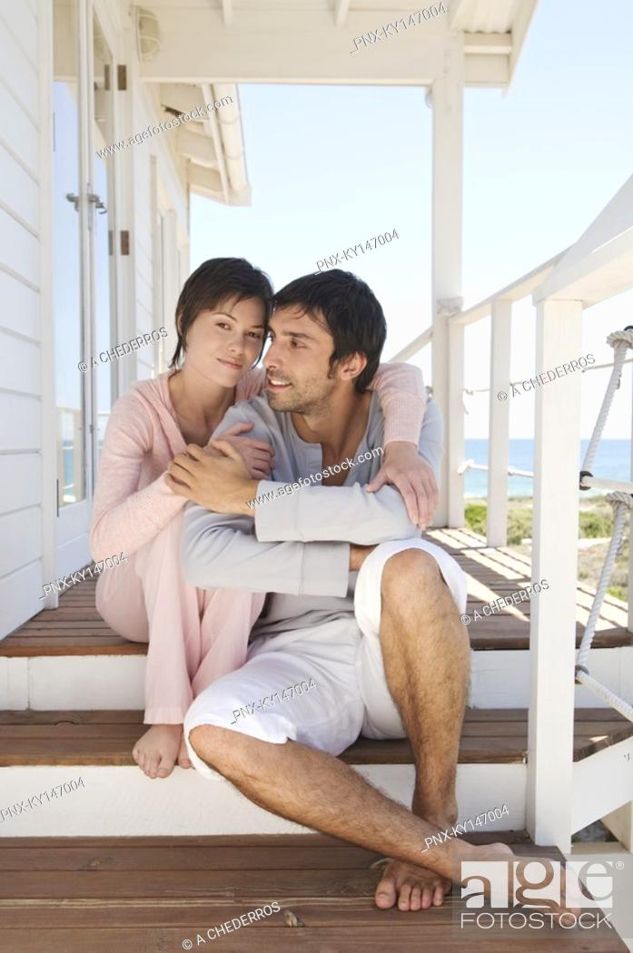 Stock Photo: Couple embracing, sitting on wooden terrace.