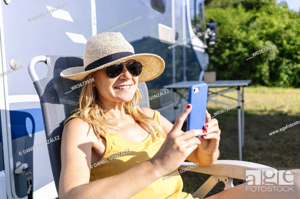 Stock Photo: Relaxed woman sitting next to camper enjoying vacation and using smartphone.