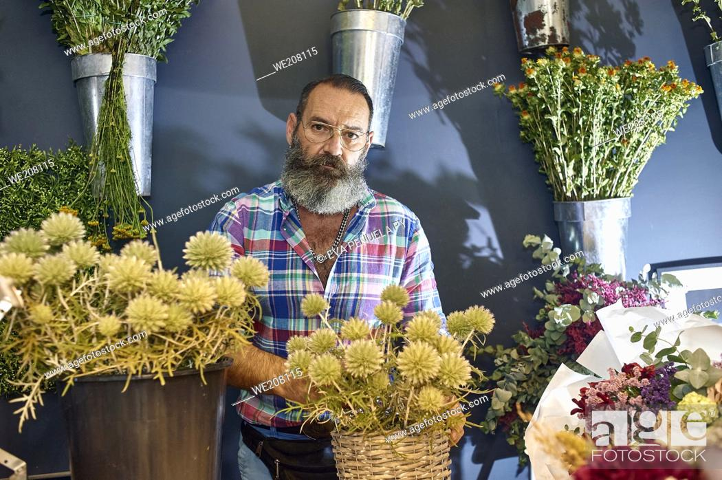 Stock Photo: A florist taking care of various flowers and bouquets in his shop.