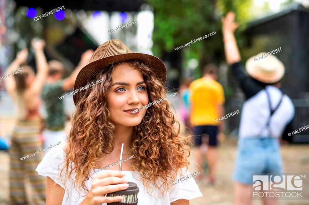 Photo de stock: Front view of a beautiful young girl at summer festival, holding drink.